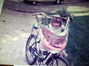 """Little girl with a newspaper boy's bicycle with the """"Long Island Press"""" bag"""