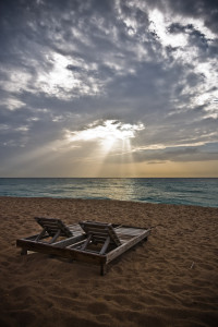 Two wooden chairs on the beach at sunset
